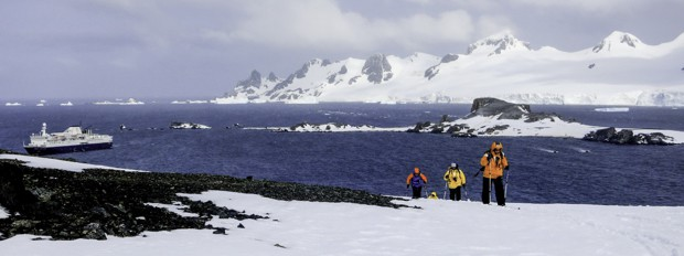 Group cross country skiing in Antarctica with their small expedition cruise ship in the background.