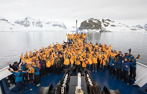 Entire crew and guests posing with their hands up in the air on the bow of their small ship in Antarctica.