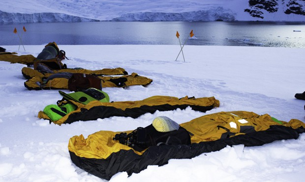 Bivy sacks lined up in the snow for camping excursion guests to sleep over night off their small ship in Antarctica.