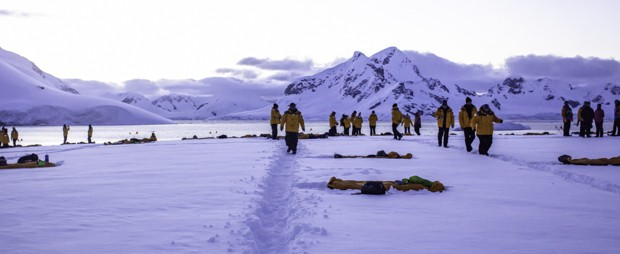 People walking in the pathway created in the snow on Antarctica to get around their campsite for the night.