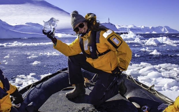 Happy guest from a small ship aboard a skiff excursion posing with a piece of glacial ice with icebergs behind in Antarctica.