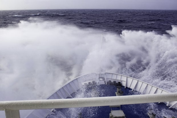 The rough seas splashing over the bow of a small cruise expedition ship during the Drake Passage returning from Antarctica.