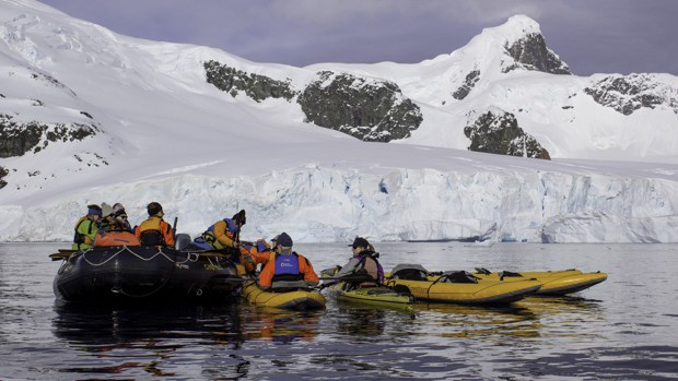 Small ship cruise guests entering kayaks from skiff in Antarctic.