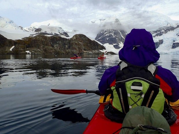 Guests from small ship cruise kayaking close to land in Antarctica.