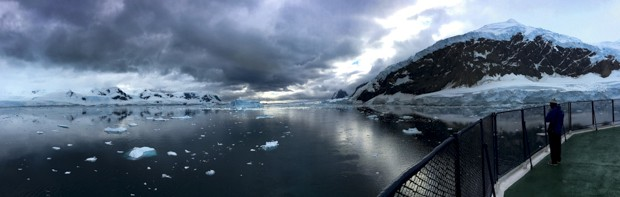 A panorama of the bow of the ship coming into Antarctica with sea ice and mountains and lots of dark clouds.