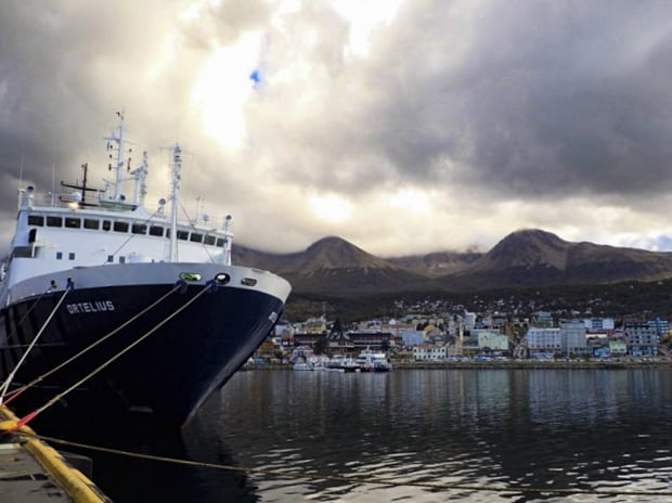 Ortelius ship anchored in Ushuaia with the city and mountains in the background.