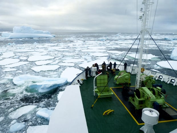 People on the bow of their small ship watching as the ship breaks through some ice in Antarctica.