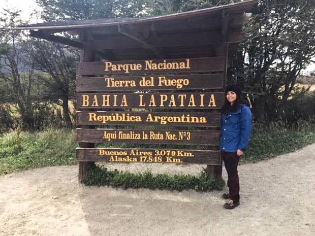 Person smiling in front of the Tierra del Fuego National Park entrance sign in Ushuaia Argentina.