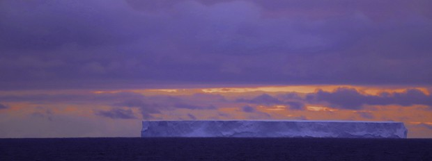 Tabular iceberg with the sunset in Antarctica, seen from a small ship cruise.