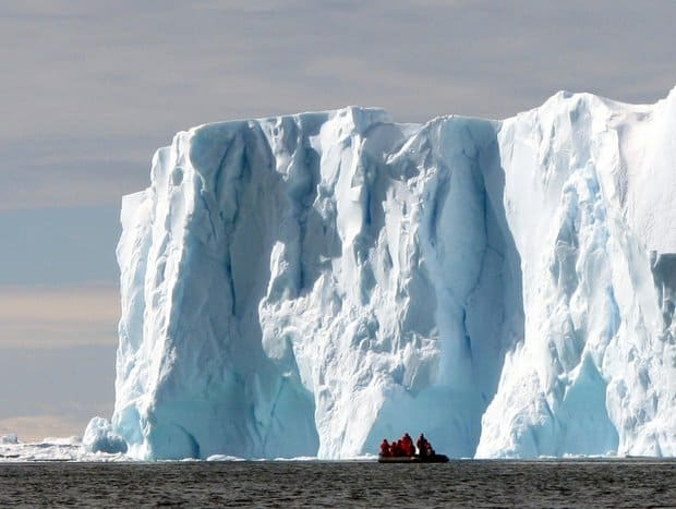 Guests off a small ship cruise on a skiff excursion in front of a massive glacier in Antarctica.