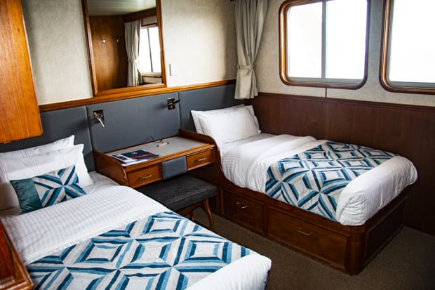 A cabin in the Coral Expeditions II with two twin beds, little desk and windows.
