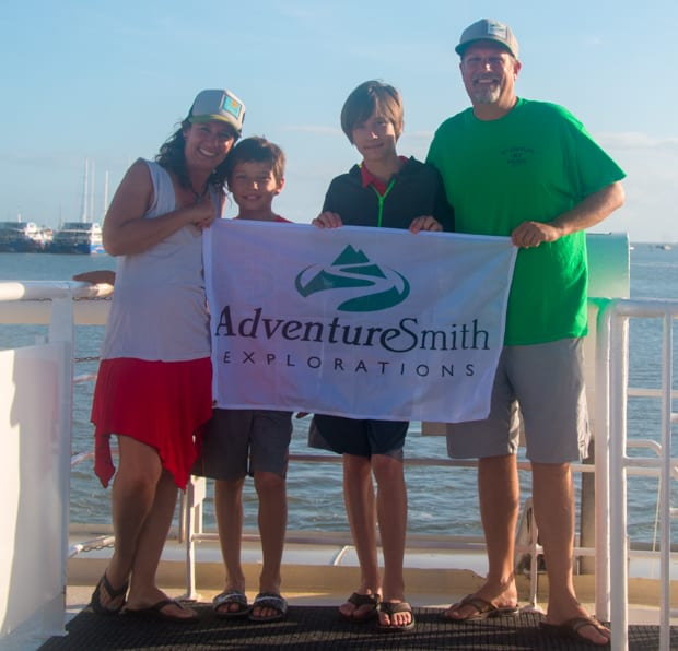 Todd and his family holding an AdventureSmith Explorations flag on the dock after a Great Barrier Reef small ship cruise.