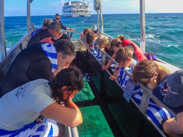 A group of Great Barrier Reef travelers on a glass-bottom boat looking down at the reef.