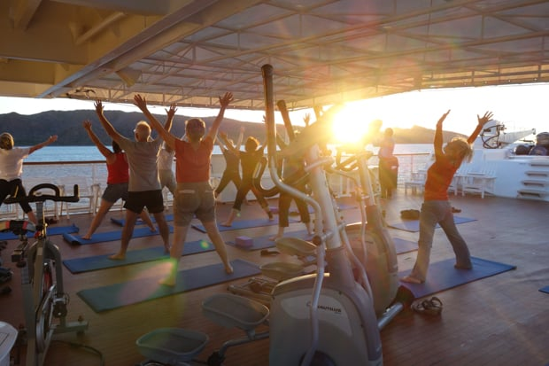 Morning Baja travelers doing yoga on the deck of a small ship cruise.