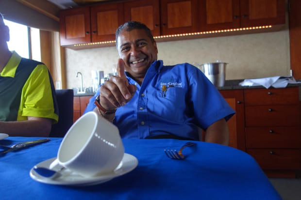 Uncruise small ship crew member relaxing at a table on the boat.