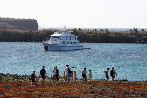 Family charter group walking on the shore in front of their small ship in the Galapagos Islands