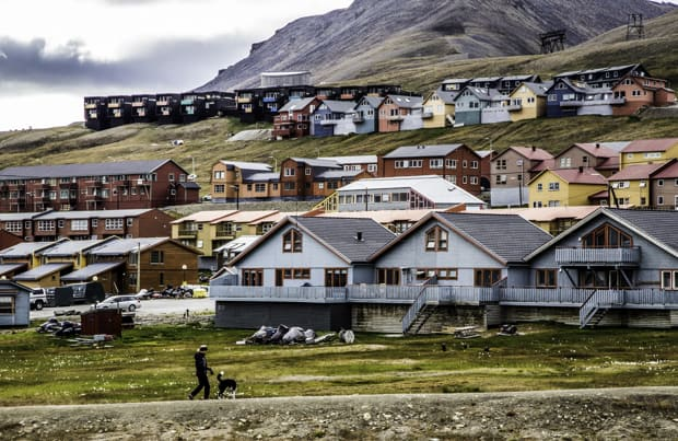 Colorful Houses in Longyearbyen with a person walking a dog in the foreground