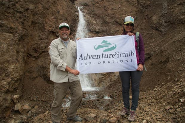 A man and a woman holding a banner in front of a waterfall in Alaska.