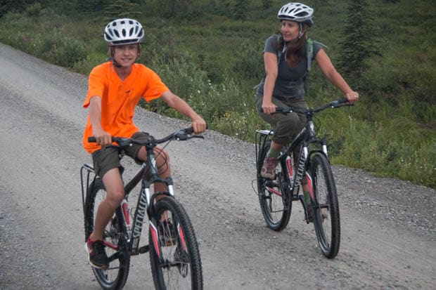 A mom and son riding bikes in Denali National Park.