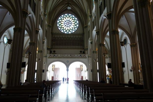 Interior of the cathedral with high vaulted ceilings, pillars and pews lining the floor of the church in Guayaquil.