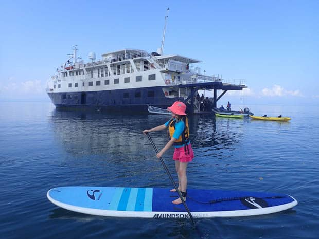 Child stand up paddling boarding in front of a small ship cruise in Costa Rica and Panama.