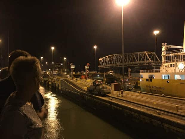 Couple standing on the deck of their small ship cruise watching the operations of going through the locks in the Panama Canal during the evening time.