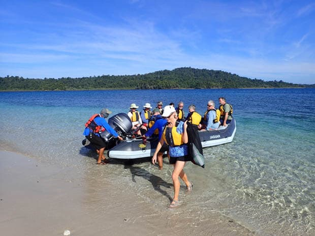 Guests getting off a skiff and onto a beach on a tour from a small ship Costa Rica and Panama cruise.