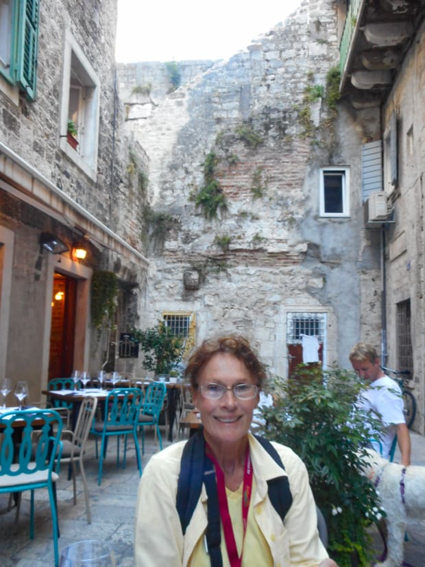 Cafe tables and stone cobbled buildings surrounding a courtyard with a happy traveler in Dubrovnik, Croatia.