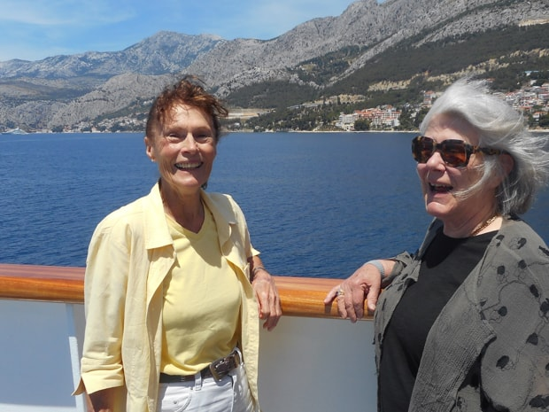 2 happy traveling ladies on the balcony deck of the small motor yacht Futura while sailing.