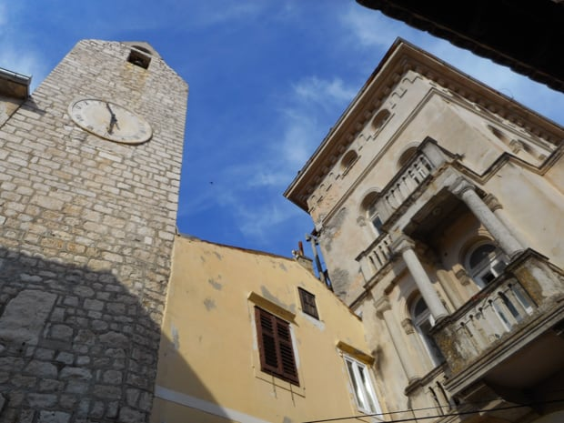 Old buildings with large windows and pillars next to a cobblestone clock tower Dubrovnik, Croatia.
