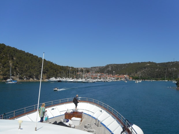 Bow of the motor yacht Futura cruising into the bay of a Greek town and marina.