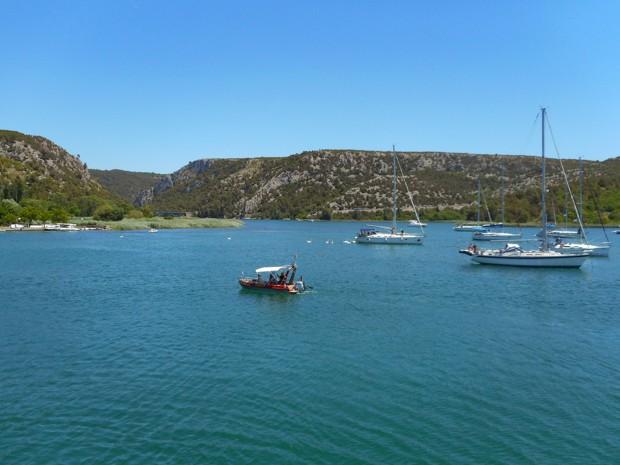 Several anchored sailboats with a small water taxi motoring people toward land.