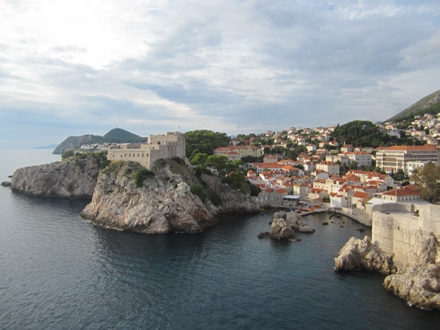 View from a small ship cruise of the city of Dubrovnik Croatia surrounded by cliffs, walls, and mountains.