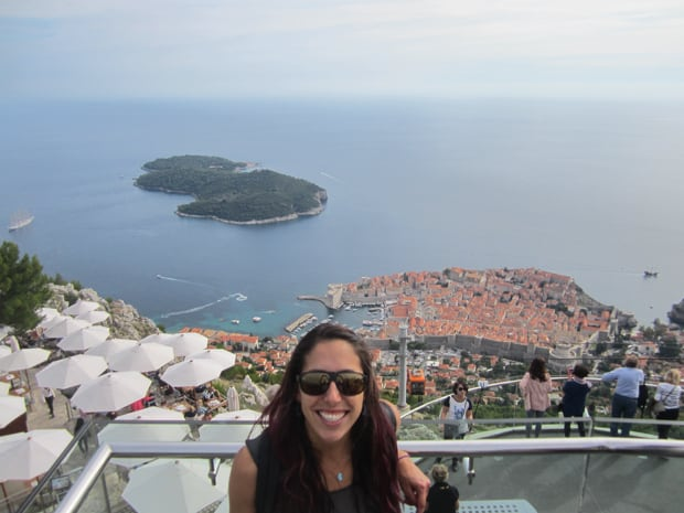 Guest from a small ship cruise in Croatia smiling at the top of the cable car with Dubrovnik below her.
