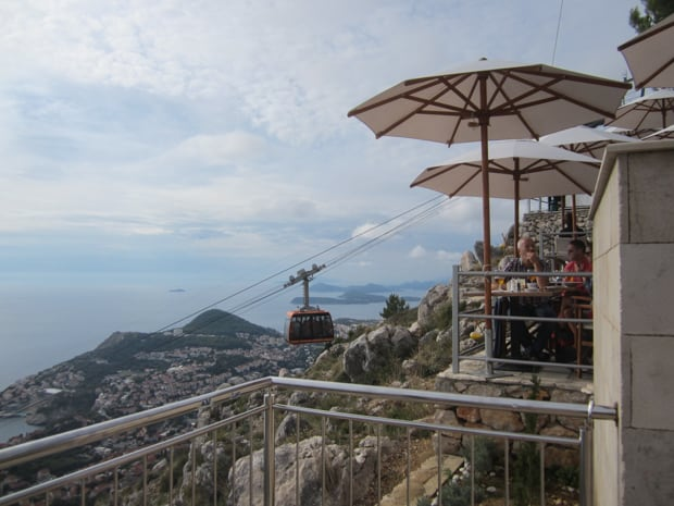 View from the top of the cable car in Dubrovnik above the city with cafes at the top of the tram.