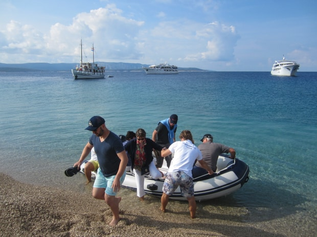Guests getting off a skiff onto the beach in Croatia with their small ship in the background next to two yachts.