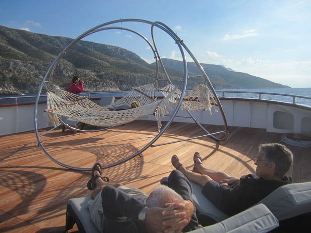 People in lounge chairs and hammocks on deck aboard their small ship cruise in Croatia.