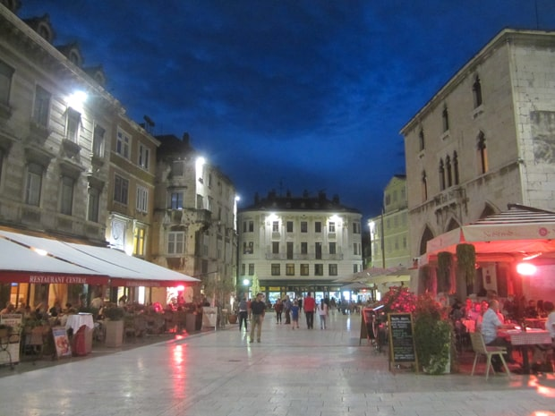 The old town plaza in Split in the evening with people sitting at cafes.