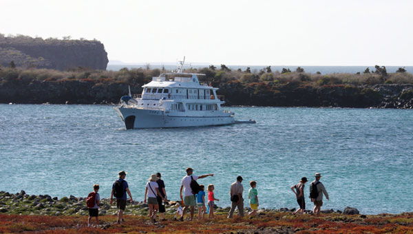 A family of Galapagos travelers walks along shore while a Galapagos yacht rests in the background