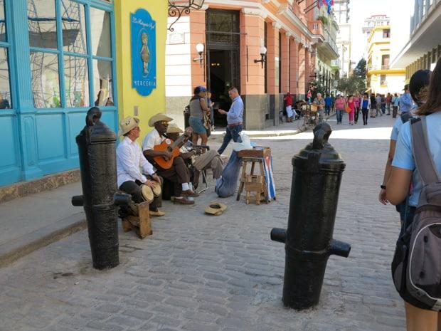 Locals sitting on the sidewalk curb playing music in Havana Cuba.