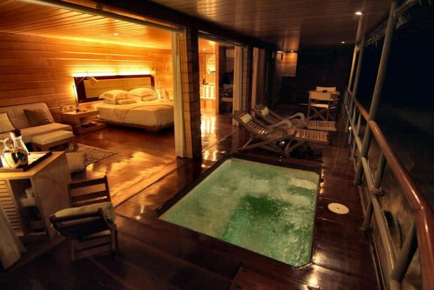 A room aboard the Defin I with a hot tub on the balcony.