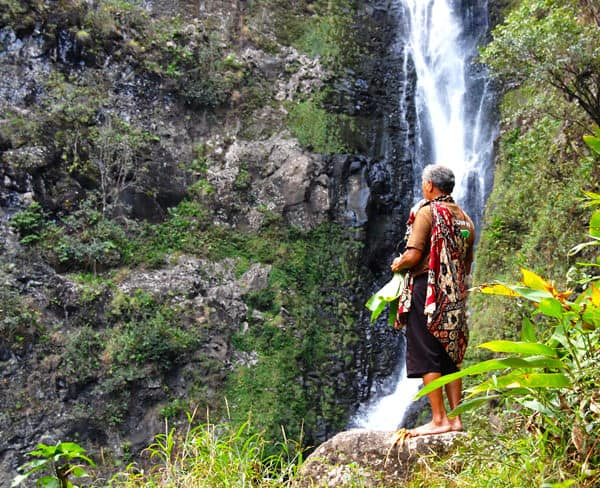 Hawaiian man standing in front of a waterfall