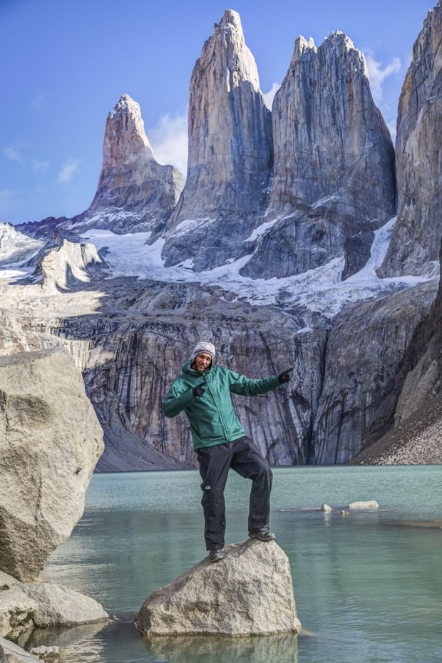 Happy traveler pointing while standing on a rock in the lake below large granite towers in Patagonia.