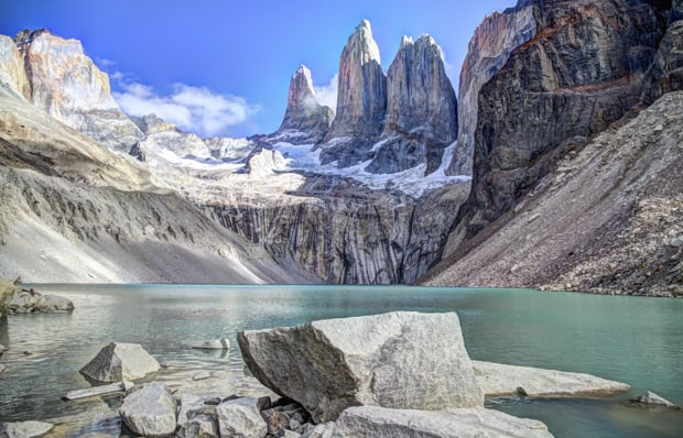 Landscape of a glaciated teal blue lake with sheer rock mountains and granite towers with snow on Patagonia land tour Towers Base hike.