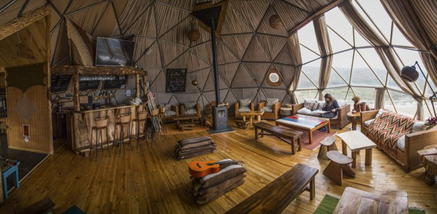 View of the lobby in the dome of the EcoCamp with couches, chairs, tables and bar looking out into the valley of Patagonia.
