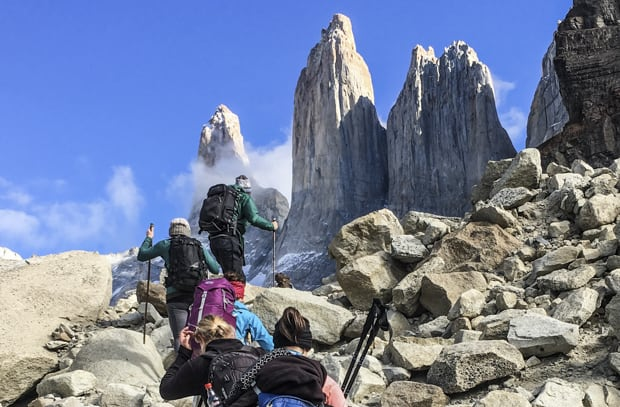 Travelers hiking up a rocky trail to 3 rock spires on a Torres del Paine Patogonian land tour.
