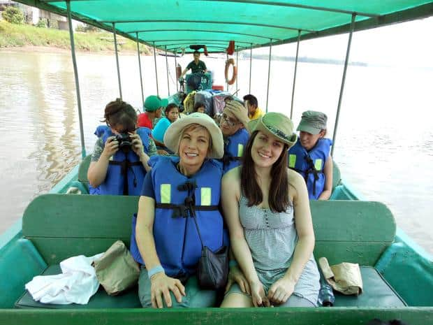 A group of travelers on a boat in the Amazon traveling on a river.