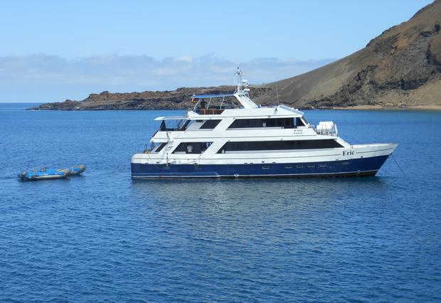 Small ship cruise Letty anchored with 2 zodiacs floating behind the stern in the Galapagos.