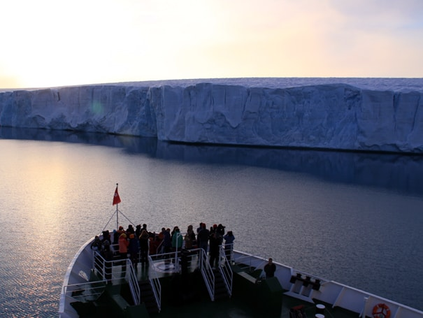 Group of small ship travelers on the bow of the M/S Expedition looking a massive tidewater glacier wall.