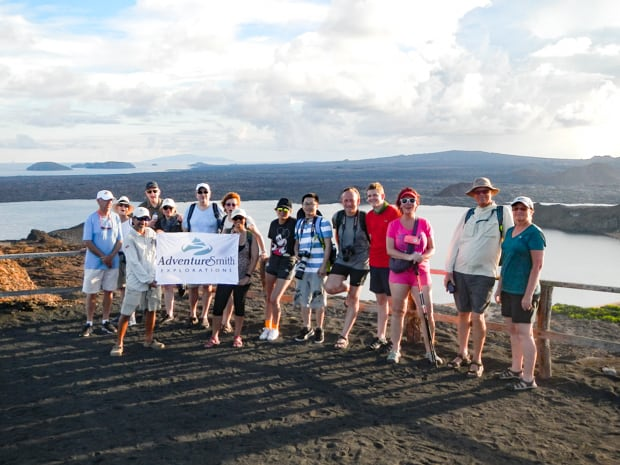 A small group of Galapagos travelers standing at an overlook holding an AdventureSmith flag